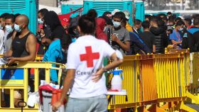 Una voluntaria de la Cruz Roja, junto a decenas de inmigrantes en el muelle de Arguineguín.
