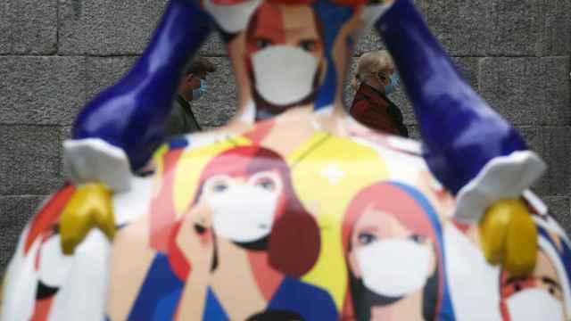 Dos personas pasean tras la figura de una menina inspirada en la Covid en Madrid.