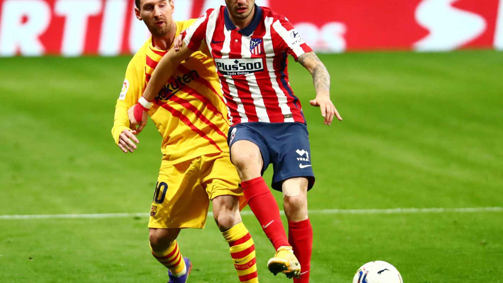 Saúl Ñíguez, perseguido por Leo Messi durante el Atlético de Madrid - Barcelona de La Liga