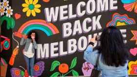 Una mujer toma una foto en el mural de  'Welcome Back', en Melbourne, Australia.