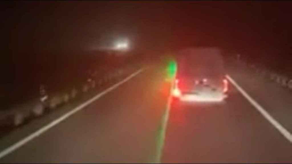 Momento en el que el conductor de la furgoneta señala con un láser al camionero que circula tras él.