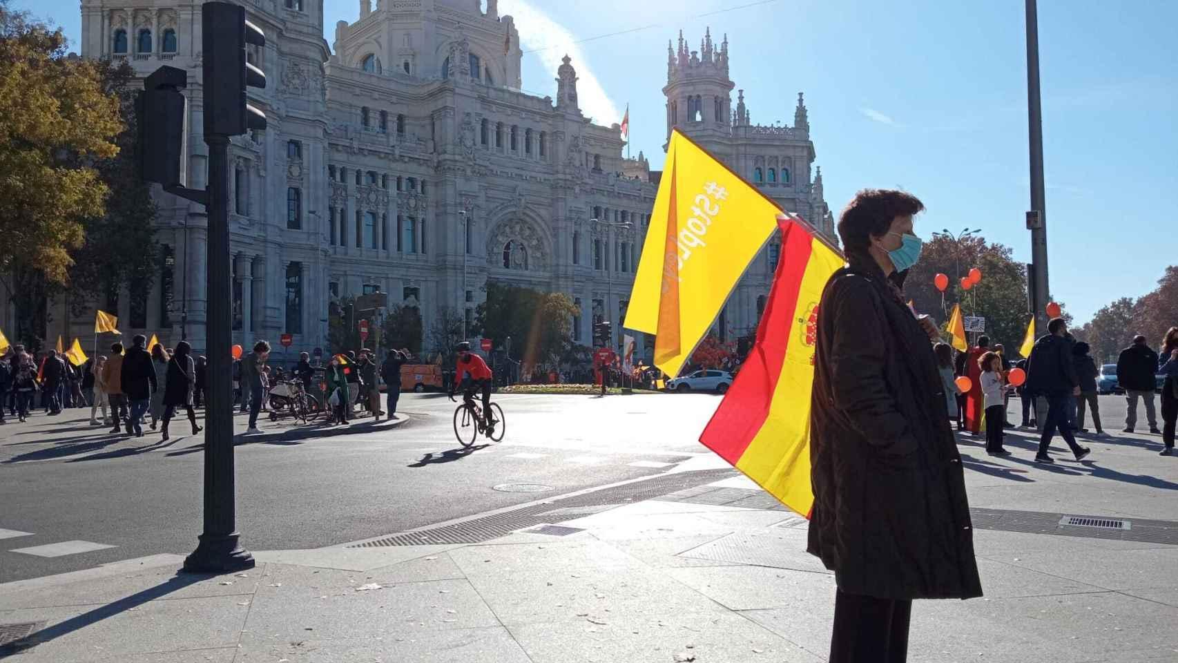 Una mujer ante el Ayuntamiento de Madrid, porta una bandera de España y una baderola contra la Ley Celaá.