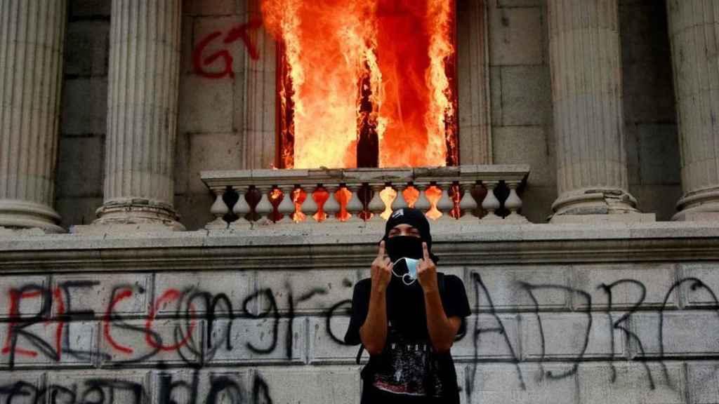 Un hombre protesta frente del Congreso de Guatemala, en llamas.