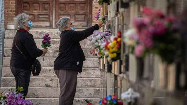 Varias mujeres colocan flores en una tumba del cementerio de Alcalá.