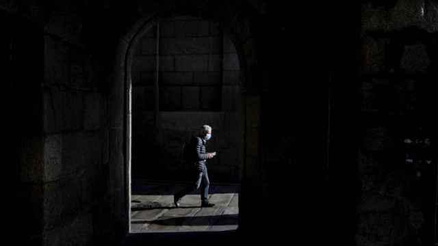 Un hombre con mascarilla camina  por el centro de La Coruña.