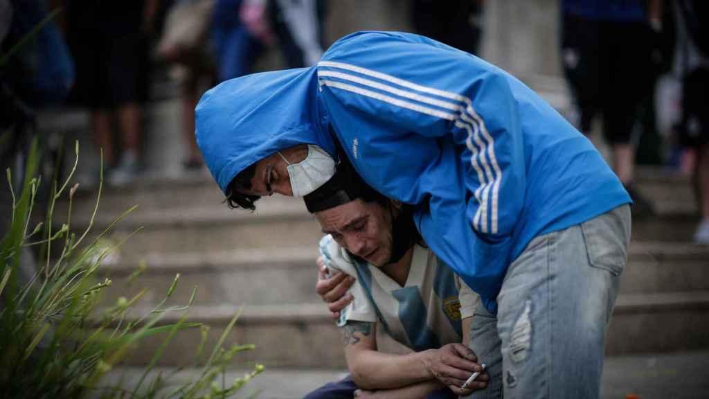 Dos personas en las puertas del velatorio de Diego Armando Maradona