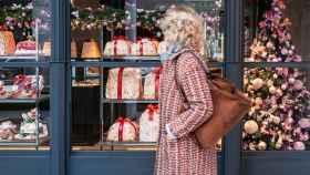 Una mujer pasea frente a un escaparate navideño.