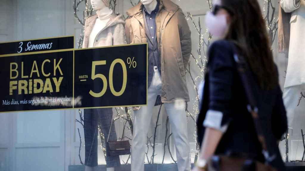 Una persona pasa ante un escaparate de un comercio con promociones.