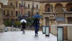 Unas personas mientras caminan este jueves por el Puente Romano de Córdoba.