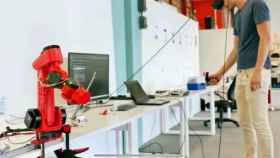 Un técnico manipula los componentes del brazo robótico, en primer plano.