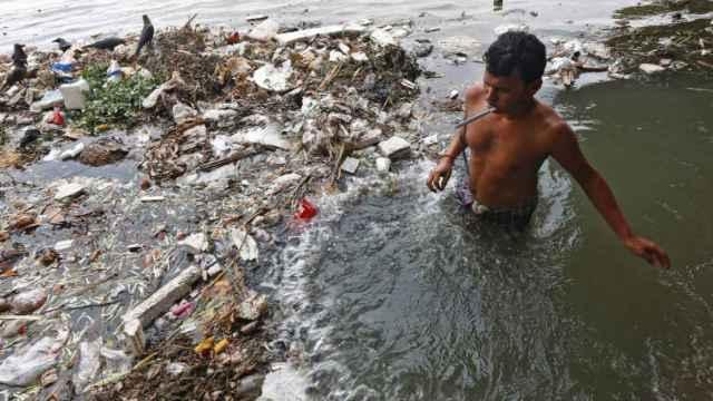 Un joven se cepilla los dientes en el agua contaminada del río Ganges en Calcuta, India.