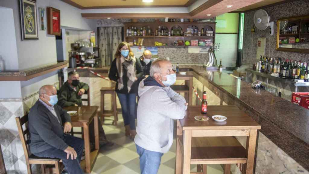 El bar del pueblo, con Tina, Paco, Teodoro y Juan José viendo las noticias.