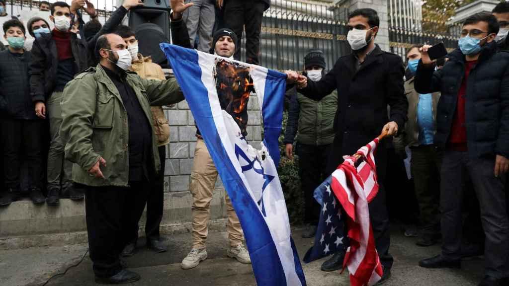Manifestantes queman las banderas de Israel y EEUU en protesta por el asesinato de Mohsen Fajrizadeh.