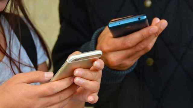 Dos personas con el teléfono móvil en sus manos.