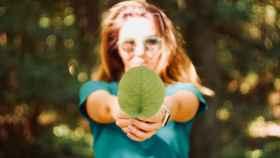 Una joven sostiene una hoja verde.