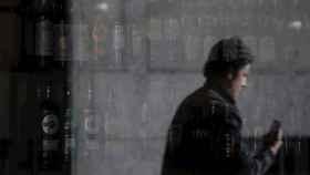 Un hombre reflejado en la ventana de un bar de La Coruña.