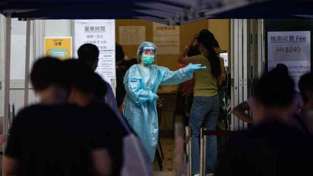 Una empleada sanitaria en un control de temperatura en Hong Kong.