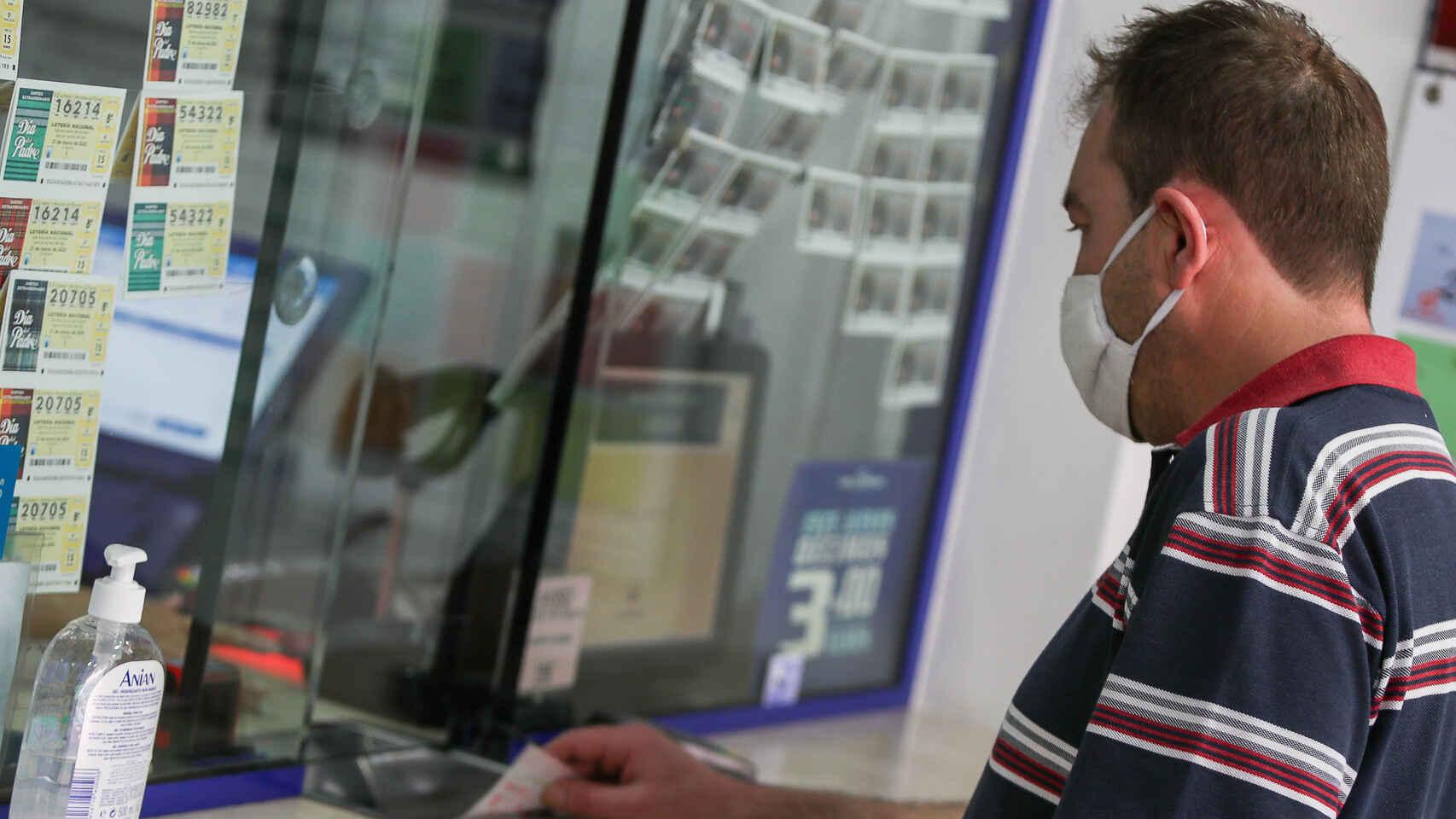Un hombre comprando en una administración de Loterías y Apuestas del Estado en Valencia.