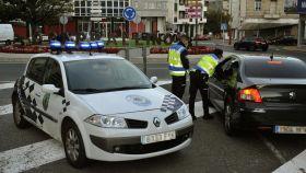 Dos agentes paran a un vehículo en un control realizado en O Carballiño, Orense.
