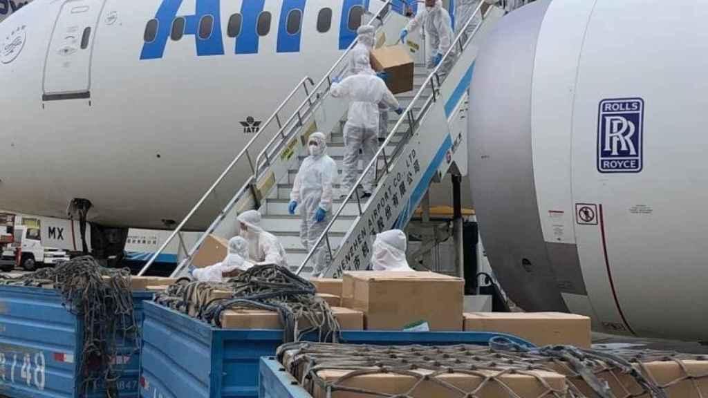 Operarios descargan material sanitario de un avión.