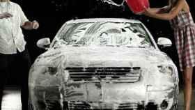 Una pareja limpiando su vehículo.