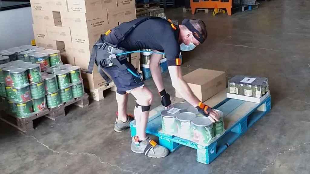 Un operario, con un exoesqueleto, carga peso en un almacén logístico.