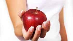 Una mujer sujeta una manzana.