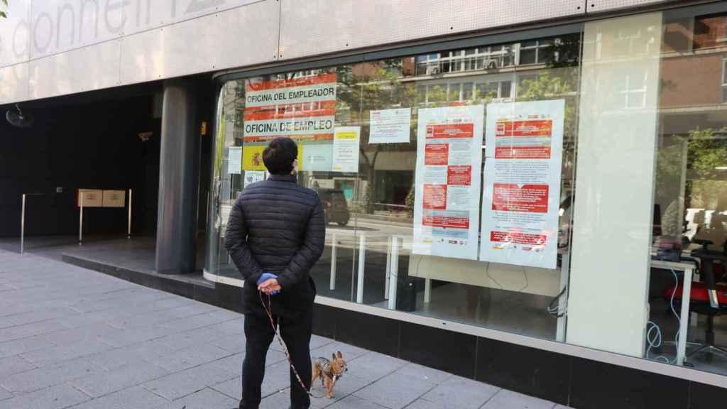 Un hombre pasa con su perro frente a una oficina de Empleo en Madrid.