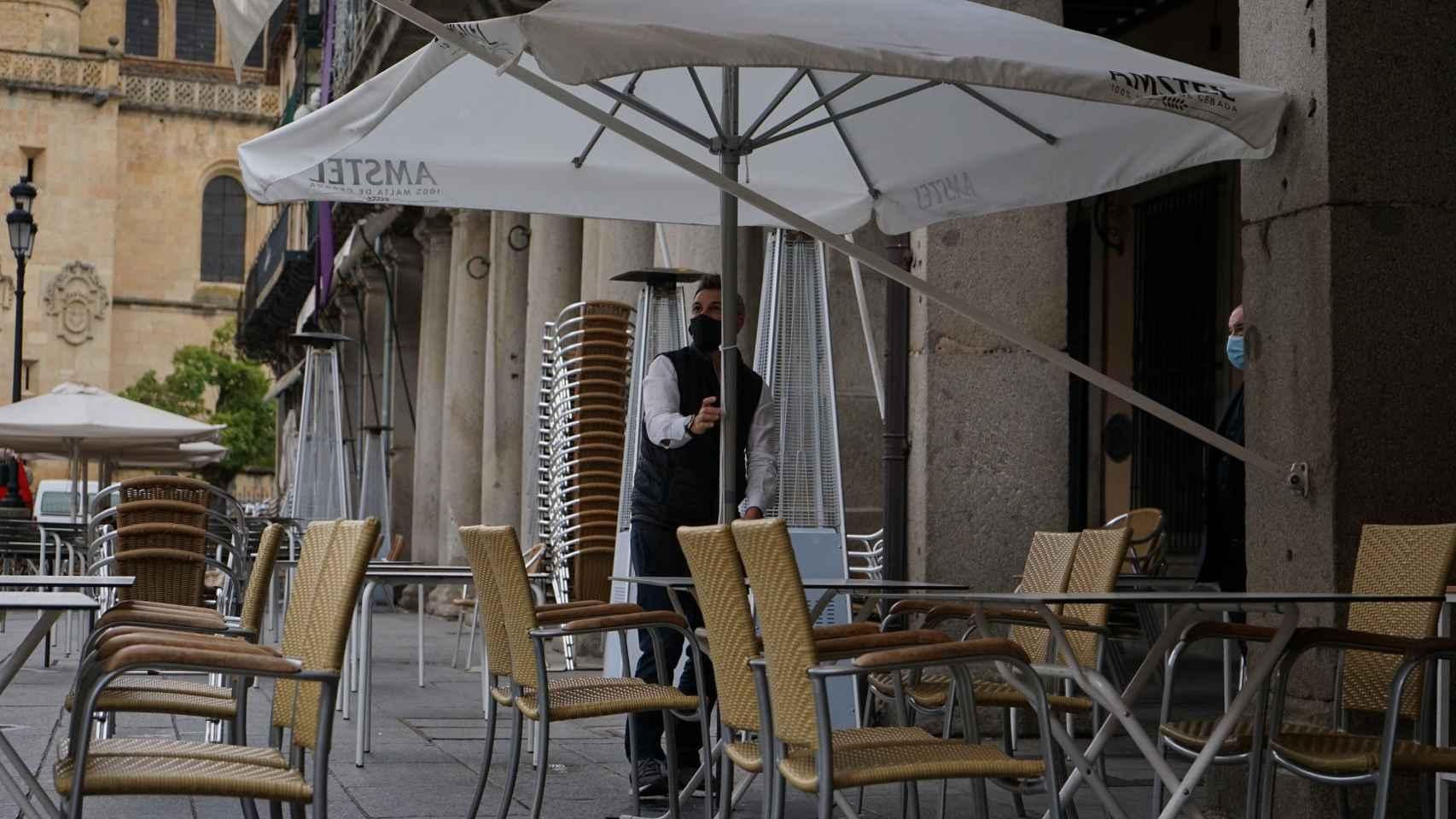 Un camarero atiende una terraza vacía.