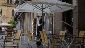 Un camarero colocando la terraza de su bar.