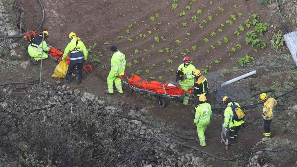 Los rescatadores, trasladando los cuerpos de los cuatro fallecidos, desde la profundidad del barranco.