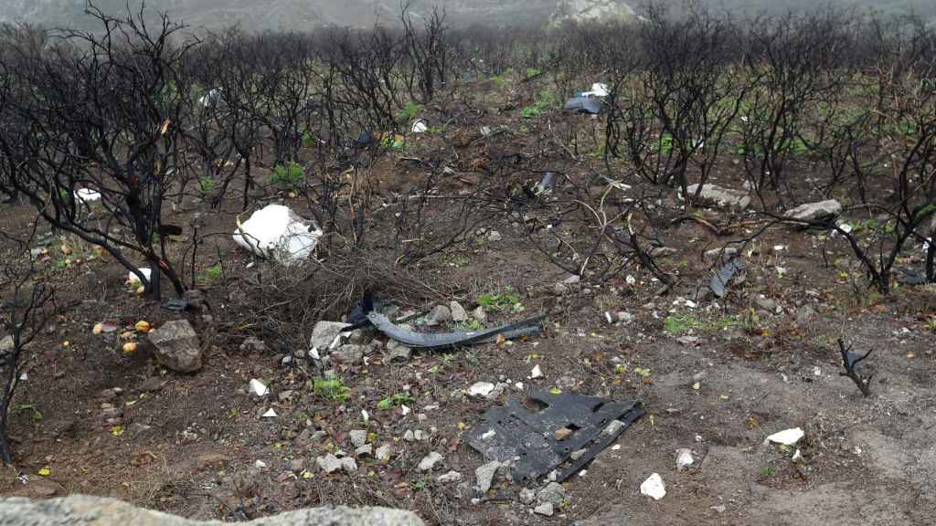 Restos del vehículo accidentado en una zona de vegetación calcinada por el incendio de 2019.