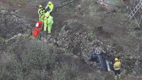 El coche accidentado en la profundidad del barranco y los operarios rescatando los cuerpos.
