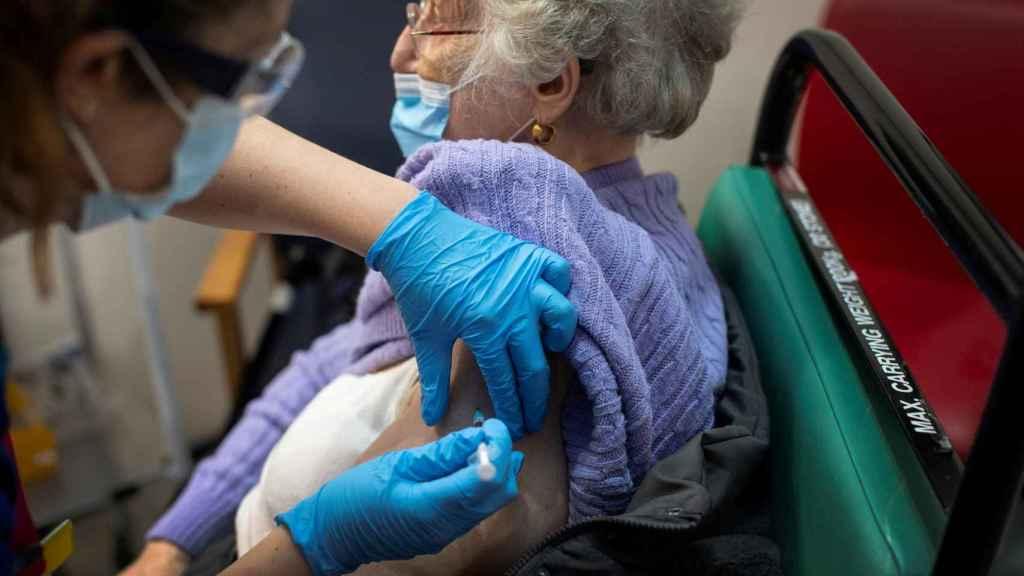 Una mujer se pone la vacuna de Pfizer.