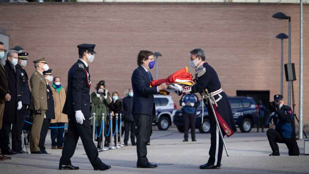 Almeida entrega la bandera nacional para su izado, en el cuartel de la Policía Municipal de Casa de Campo.