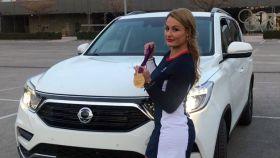 Lydia Valentín, campeona olímpica y mundial, muestra su medalla junto al coche.