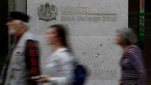 Varias personas pasan frente a la Bolsa de Londres.