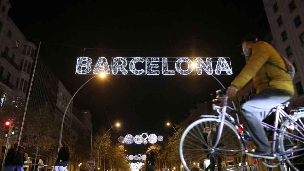 Paseantes debajo de las luces de Barcelona.
