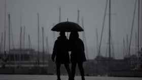 Dos jóvenes pasean bajo la lluvia.