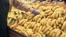 Un dependiente cogiendo plátanos de Canarias.