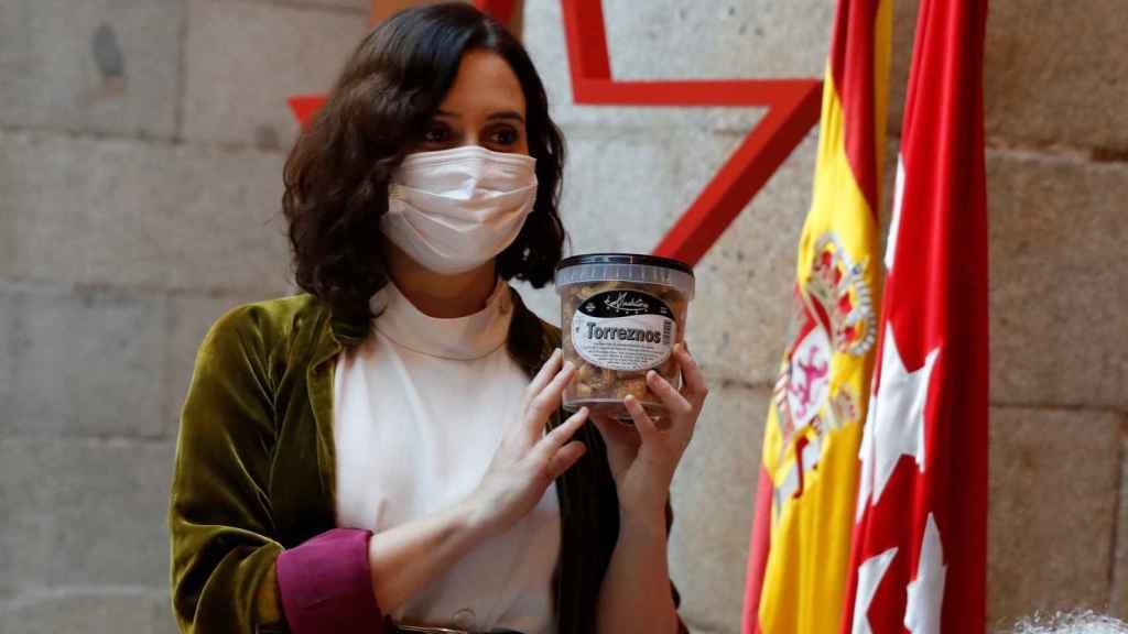 La presidenta de la Comunidad de Madrid, sujetando un bote de torreznos de La Madrileña.