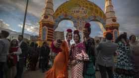 Jóvenes vestidas de flamenca posan ante la portada de la Feria de Abril.