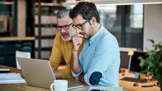 Dos hombres trabajando frente a un ordenador.
