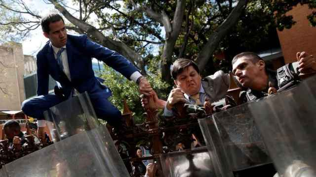 Venezuelan opposition leader Juan Guaido and other lawmakers climb on the fence of Venezuelas National Assembly building in Caracas, Venezuela, January 5