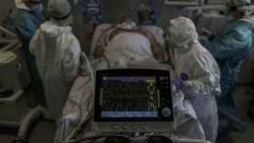 Personal sanitario totalmente protegido atiende a un paciente ingresado en la Unidad de Cuidados Intensivos del Hospital Infanta Sofía en San Sebastián de los Reyes (Madrid)