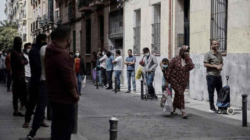 Varias personas hacen cola para recibir alimentos en el barrio madrileño de Lavapies.
