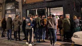 Un grupo de jóvenes se despiden ante el inminente cierre de un bar en el barrio de La Latina, en Madrid, la noche de este pasado viernes.