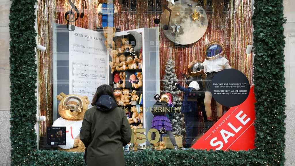 Una persona contempla el escaparate de una tienda de Amsterdam cerrada por la pandemia de Covid.