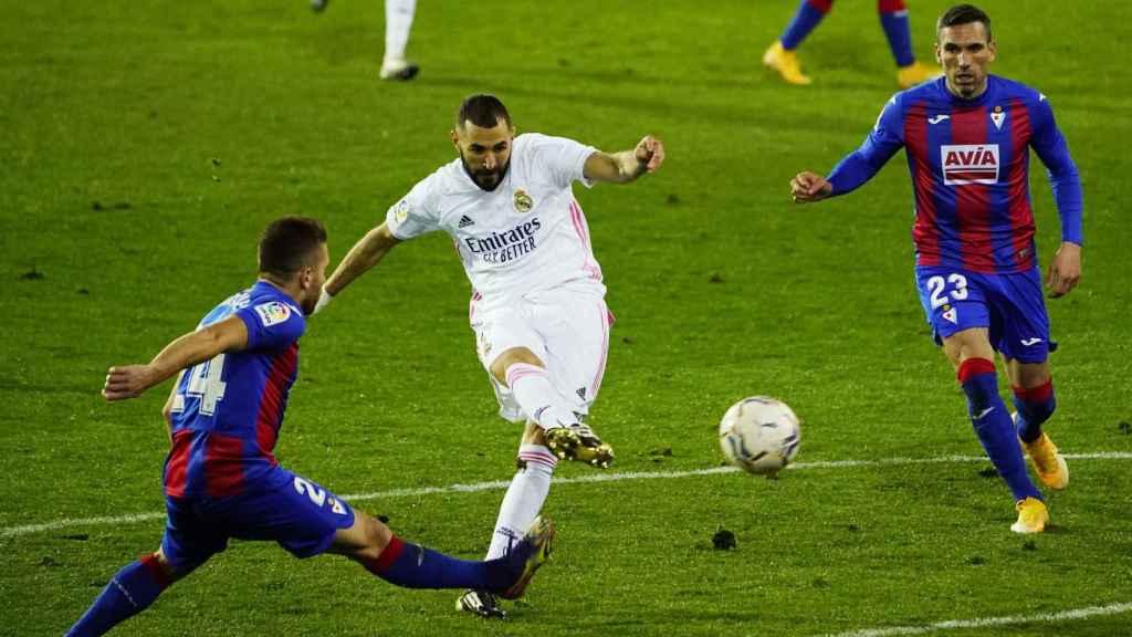 Benzema dispara a la portería del Eibar presionado por dos jugadores rivales