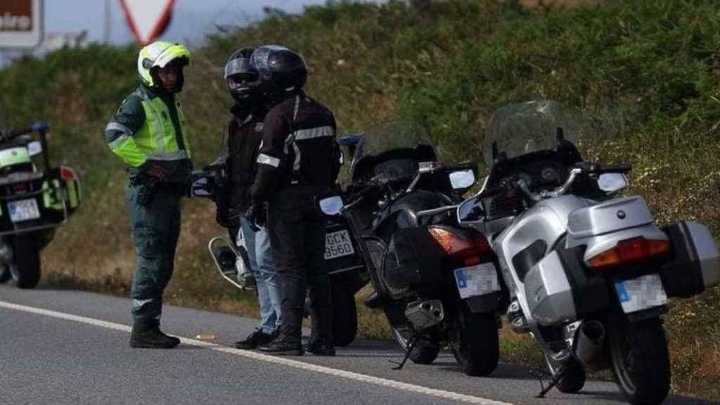 Un agente de la Guardia Civil dialoga con dos motociclistas que se han apeado de sus vehículos.